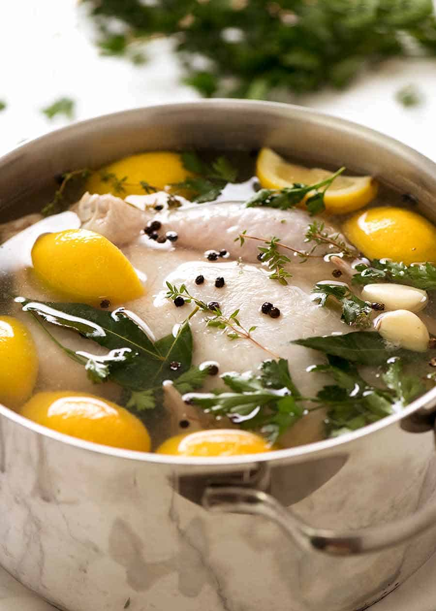 How to brine chicken - photo of whole raw chicken submerged in brine solution