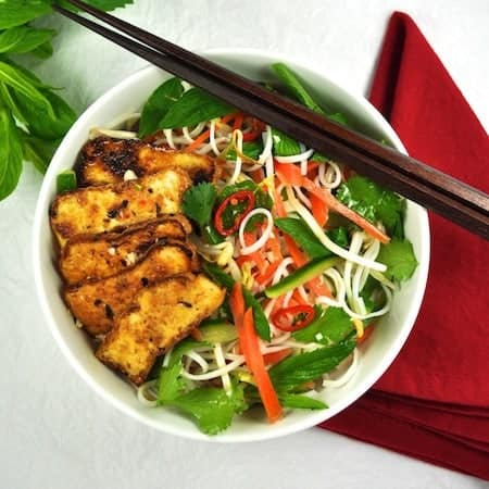 Vegetarian Vietnamese Noodle Bowl (vegan) with Marinated Tofu in a white bowl with chopsticks, ready to be eaten.