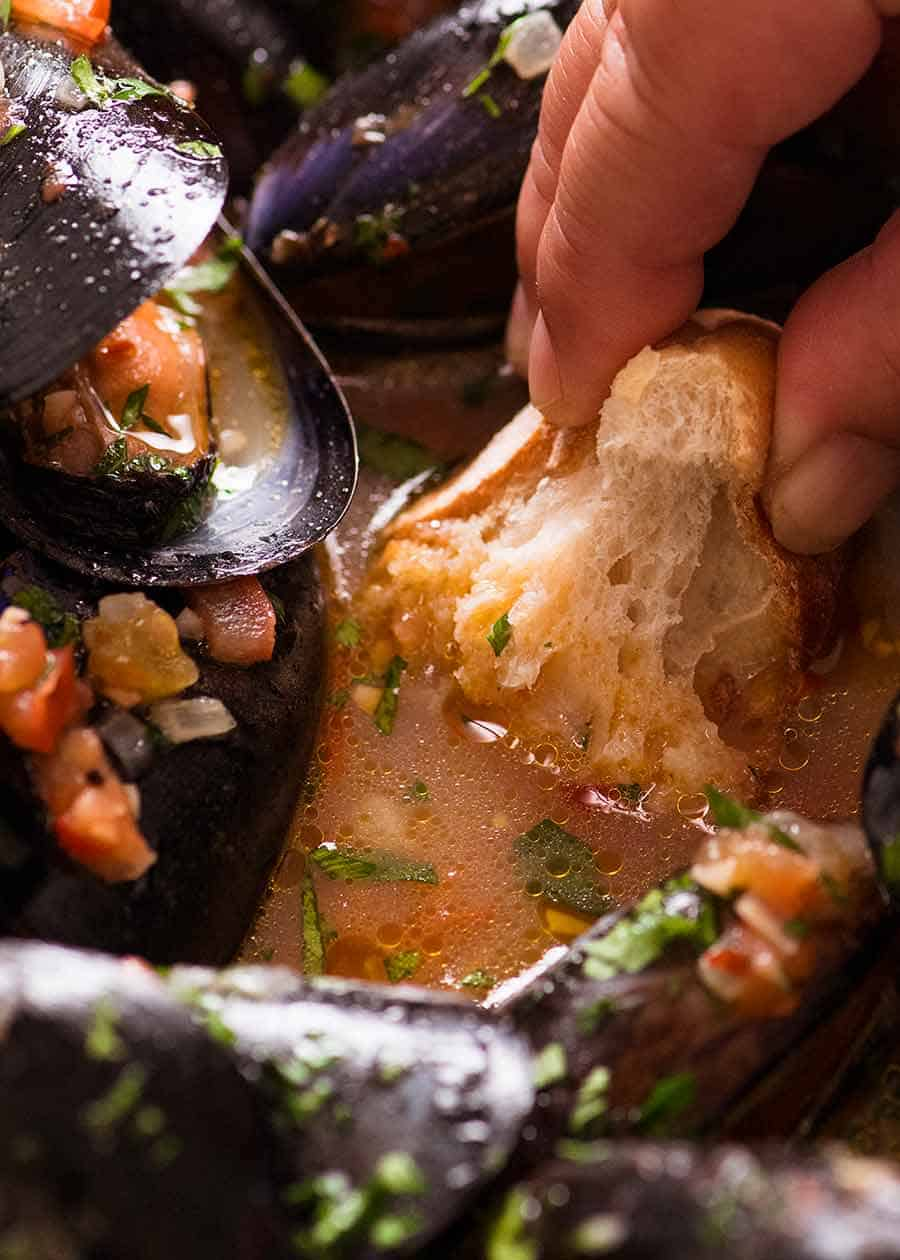 Crusty bread being dipped into mussel sauce