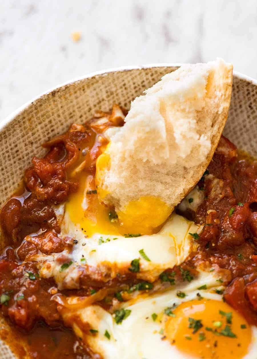 Bread being dunked into the runny yolks of Shakshuka, Middle Eastern baked eggs