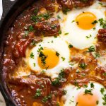 Close up of Shakshuka Middle Eastern baked eggs in a black skillet, fresh off the stove