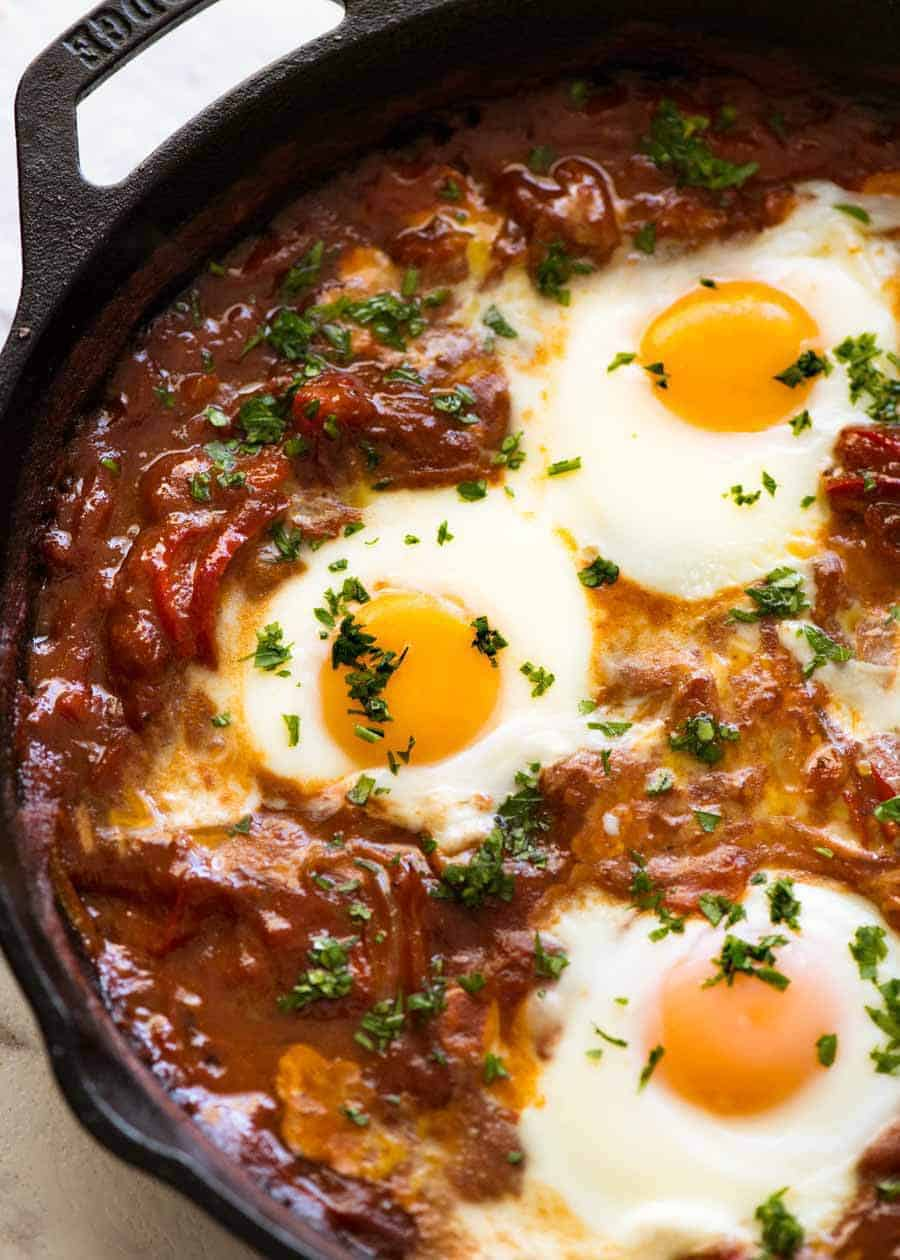 9bf1ef551d46 Close up of Shakshuka Middle Eastern baked eggs in a black skillet