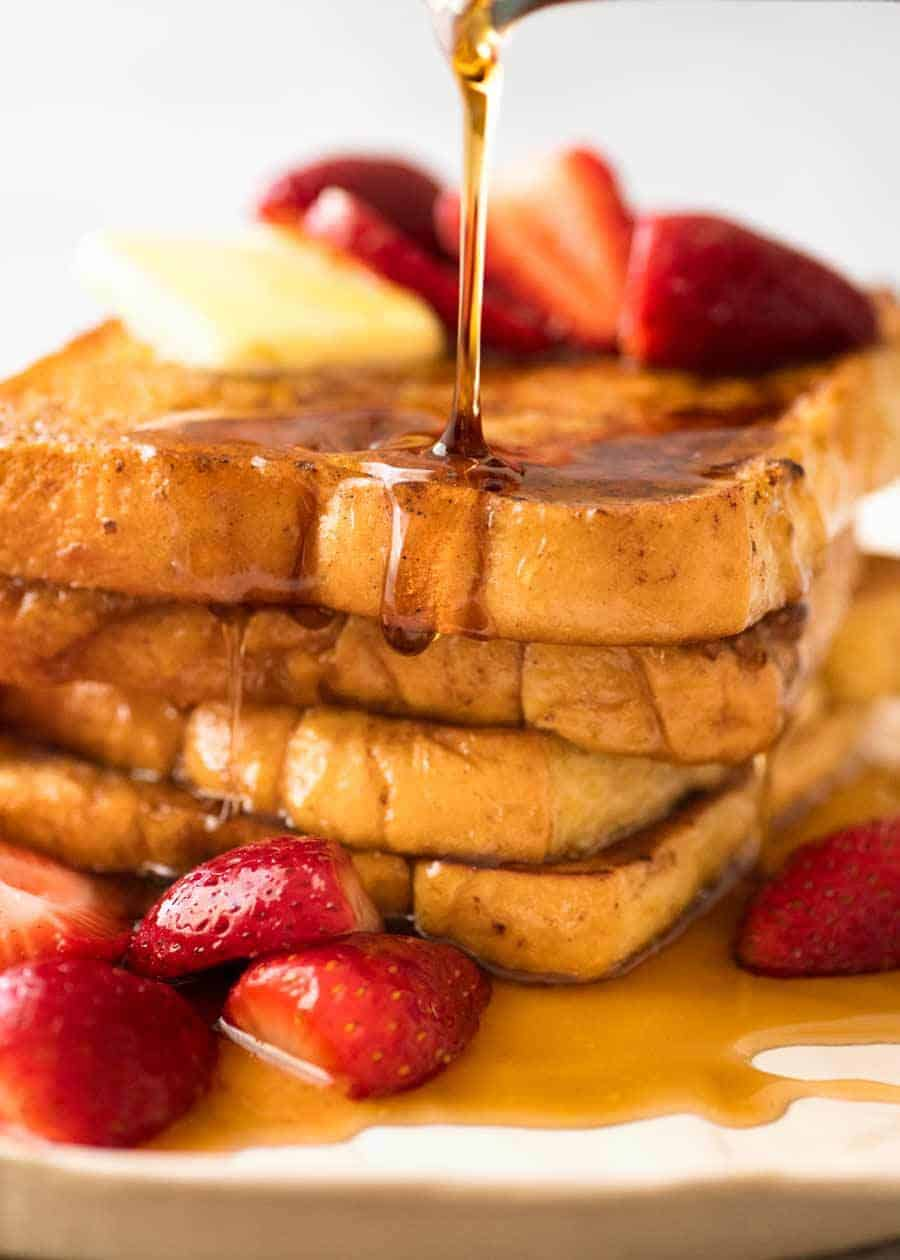 Maple syrup being poured over a stack of French Toast