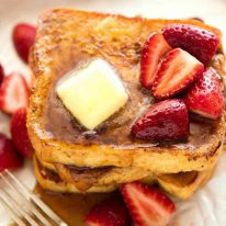 Pile of French Toast on a rustic white plate, doused with maple syrup and topped with a pat of melting butter and strawberries.