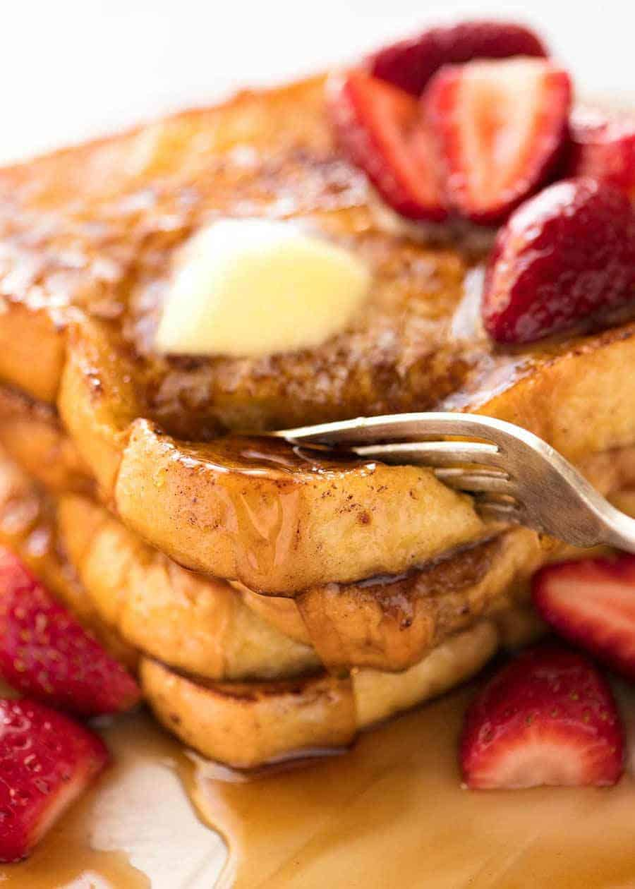Fork cutting into a stack of French Toast smothered in maple syrup