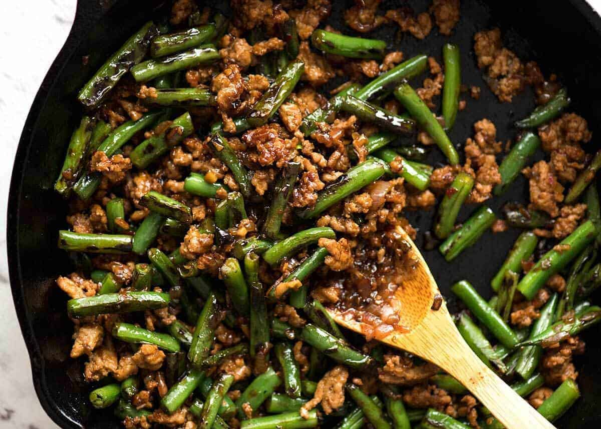 Pork Stir Fry with Green Beans in a black skillet with a wooden spoon.