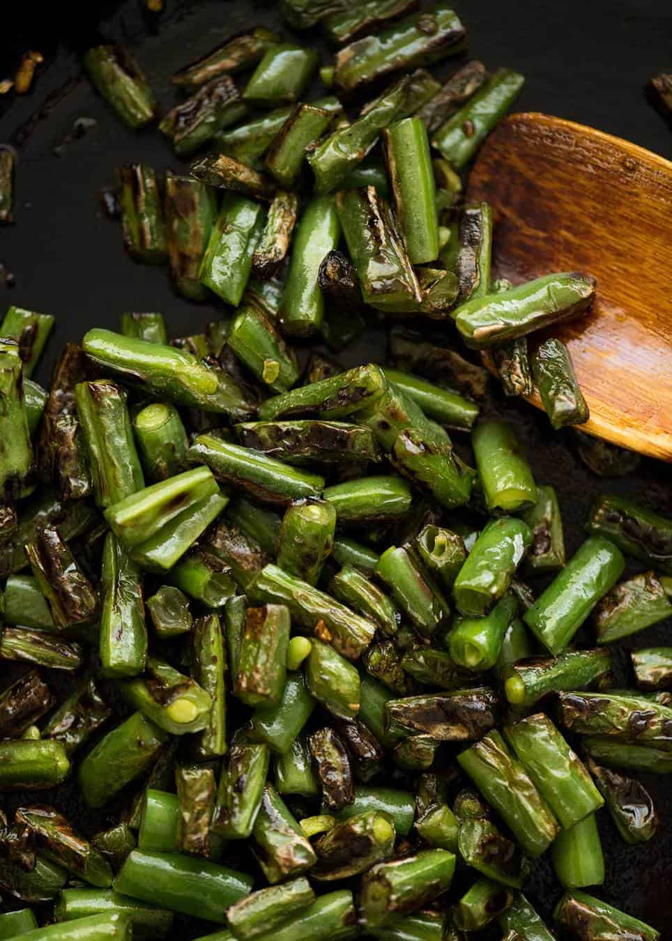 Charred chopped green beans in a black skillet with a wooden spoon.
