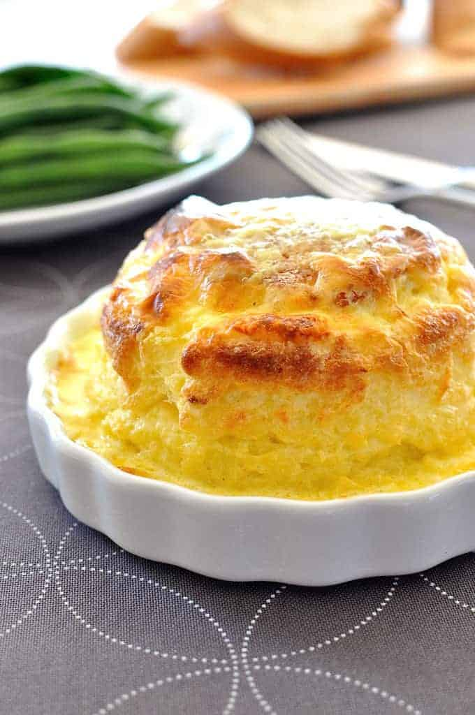 Souffle you can make ahead - freezer and refrigerator friendly. Cheesy, light as air soufflé covered in a luscious creamy sauce. And easy!