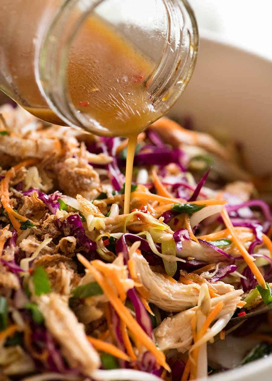 Pouring Asian dressing over Asian Slaw