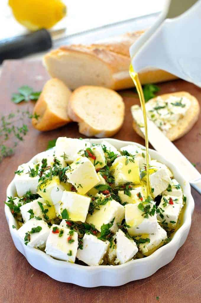 Olive oil being poured over Feta Marinated with Herbs and Chilli