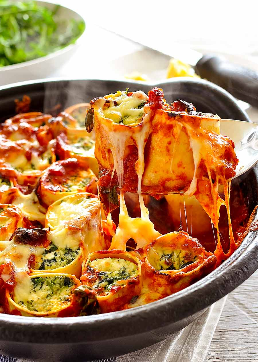 Spoon lifting up Spinach and Ricotta Rotolo - cheese pull!
