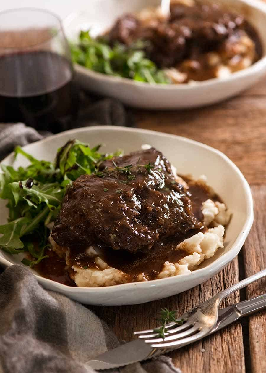 Slow Cooked Beef Cheeks with Red Wine Sauce on creamy mashed potato on a plate ready to be eaten