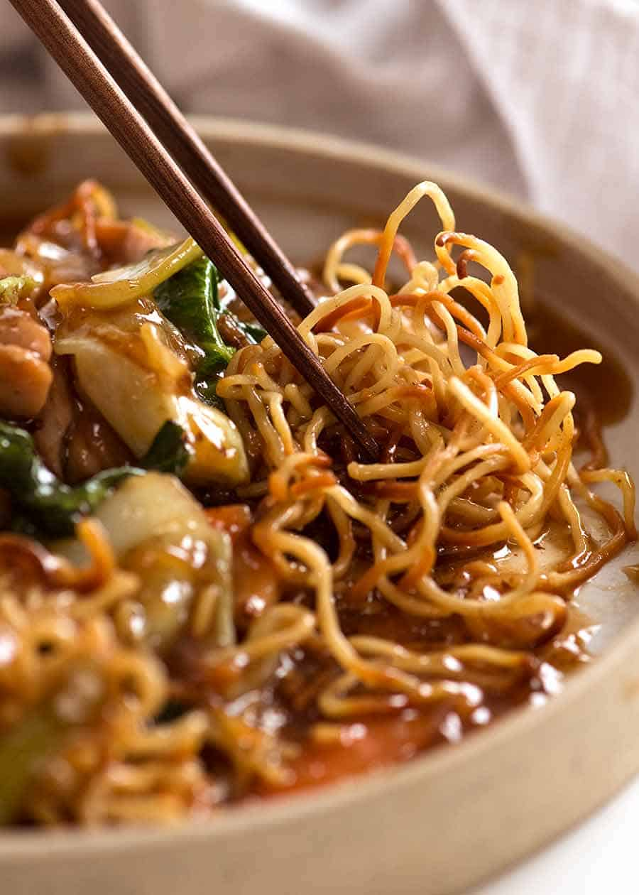 Close up photo of chopsticks picking up Chinese Crispy Noodles (Chow Mein)
