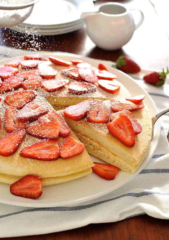 Giant pancake topped with strawberries, sprinkled with icing sugar