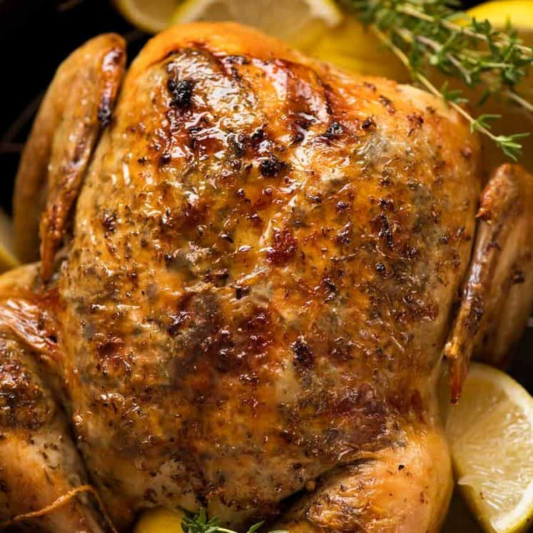 Overhead photo of Slow Cooker Roast Chicken (whole chicken) on a serving platter with lemon wedges and thyme, ready to be served