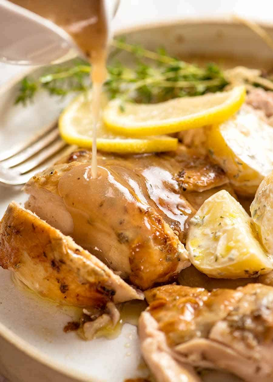 Lemon Sauce being poured over Slow Cooker Roast Chicken
