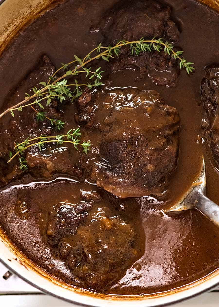 Overhead photo of Slow Cooked Beef Cheeks with Red Wine Sauce in a pot, fresh off the stove ready to be served.