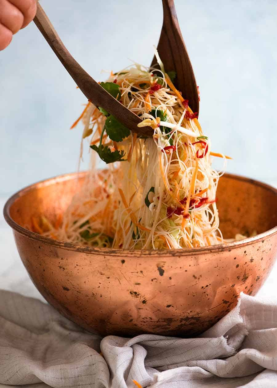 Tossing Vermicelli Noodle Salad in a rustic copper bowl