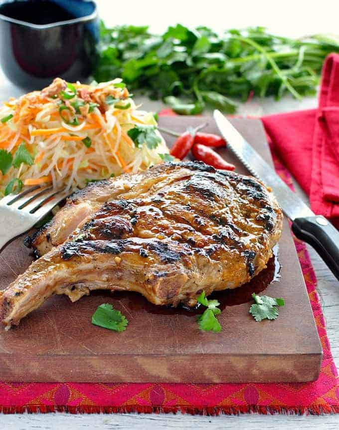 Vietnamese pork chop on a wooden board with papaya salad