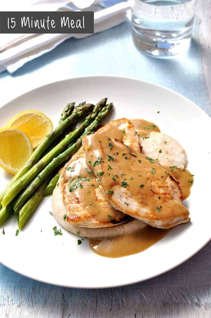 Chicken with Creamy Marsala Sauce, white bean puree and asparagus, on a white plate