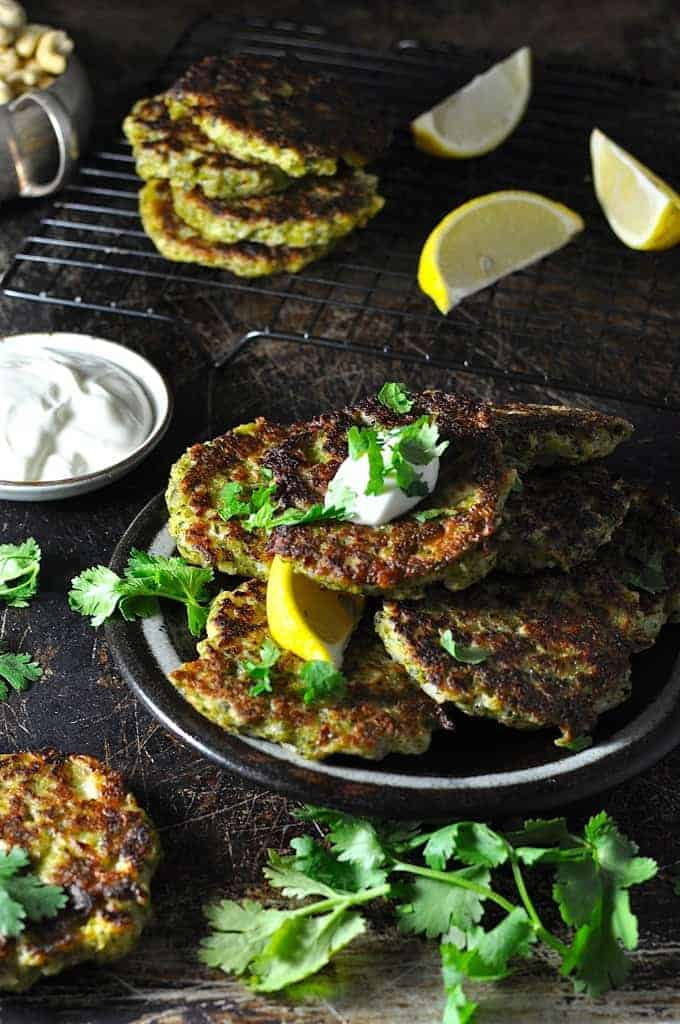 Broccoli Fritters on a plate with lemon wedge and yoghurt sauce