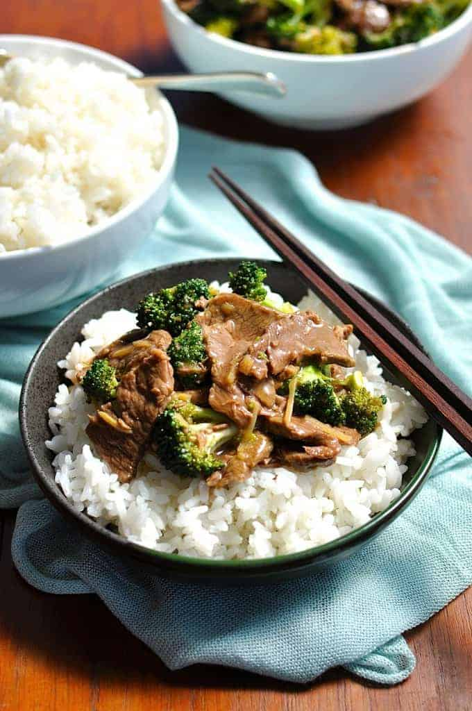 Slow Cooker Beef and Broccoli in a dark bowl with blue cloth