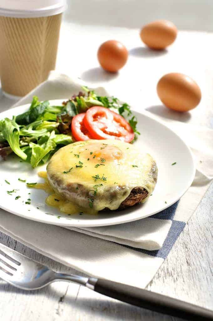 Baked Eggs in Mushrooms covered in melted cheese on a white plate with coffee on the side, ready to be eaten.