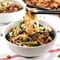Chopsticks picking up Crispy Shredded Chicken Noodle Stir Fry from a bowl.