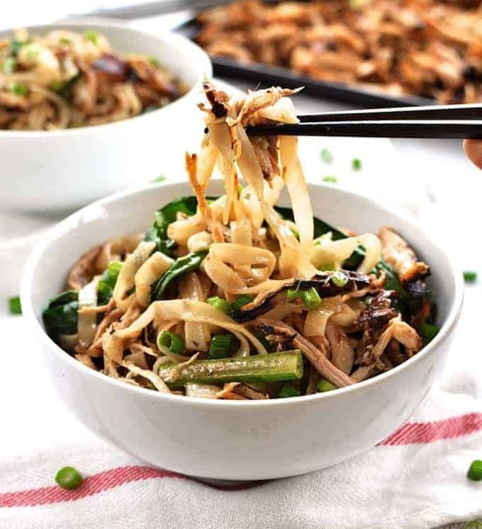 Chopsticks picking up Crispy Shredded Chicken Noodle Stir Fry from a bowl.