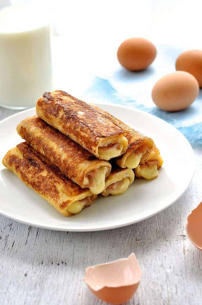 Ham and cheese french toast roll ups recipetin eats ham and cheese french toast roll ups stacked on a plate forumfinder Choice Image
