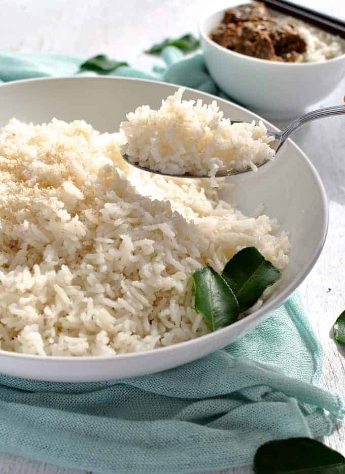 A spoon scooping up some fluffy coconut rice in a white bowl.