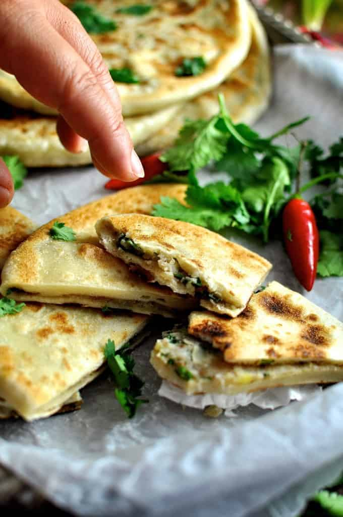 Aloo paratha indian potato stuffed flatbread recipetin eats hand reaching in to take a pice of aloo paratha indian potato stuffed flatbreads forumfinder Image collections