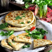 Aloo Paratha (Indian Potato Stuffed Flatbreads) filled with mashed potato and spiced beef on a tray, ready to be served.