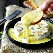 Dipping toasted bread into melting, gooey Baked Brie with Maple Syrup and Thyme