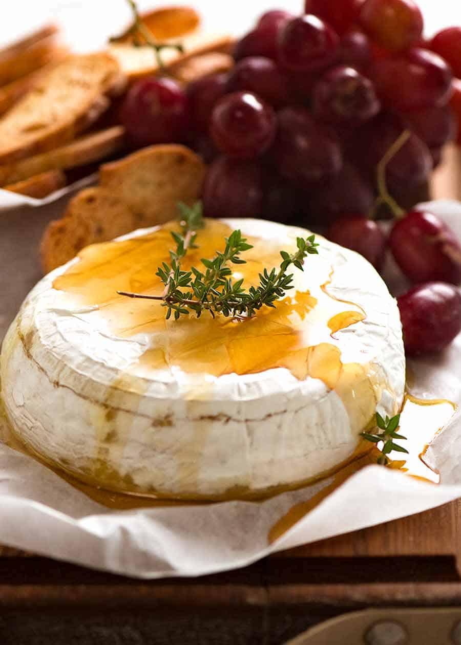 Photo of Baked Brie drizzled with honey garnished with fresh thyme, with crispy toasted bread and grapes
