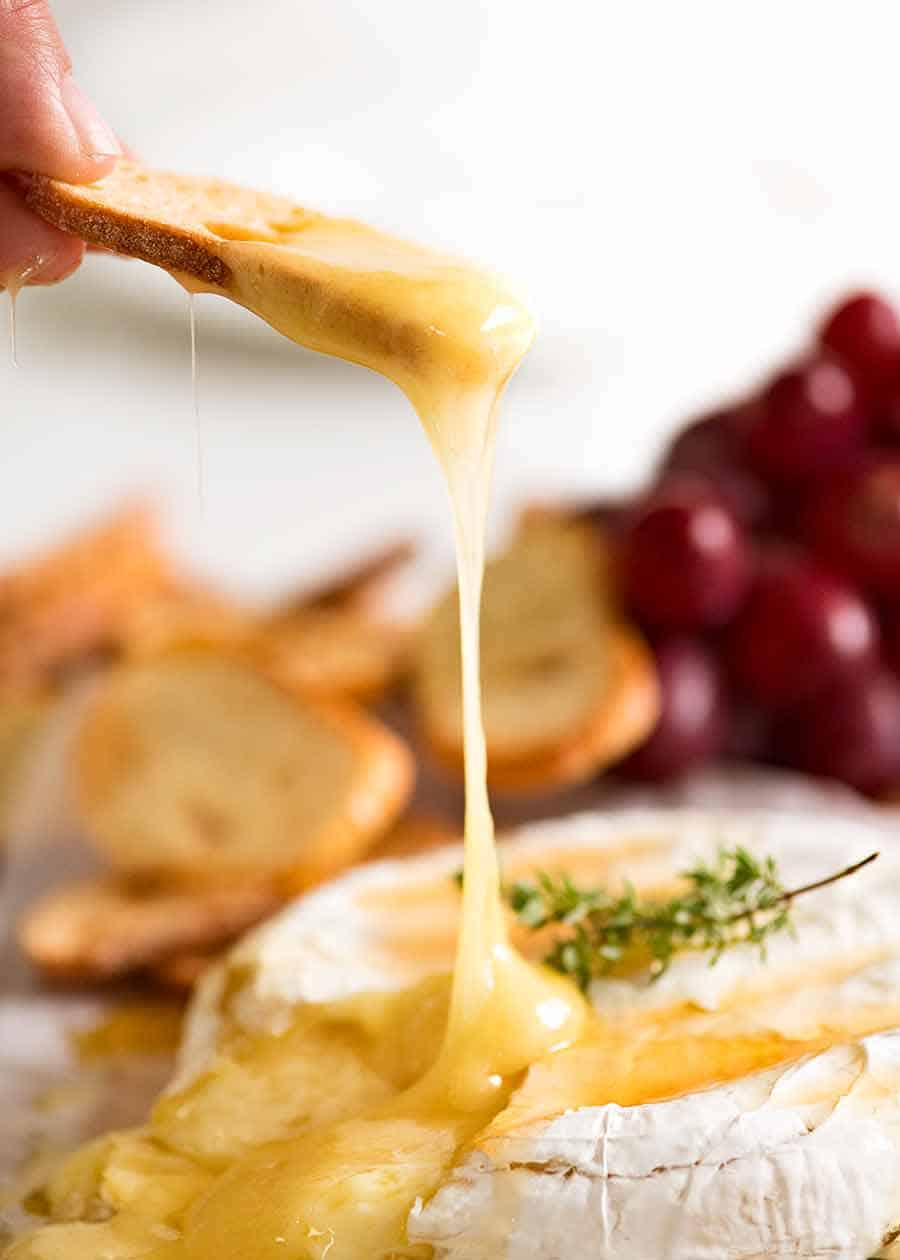 Crispy toasted bread scooping up Baked Brie