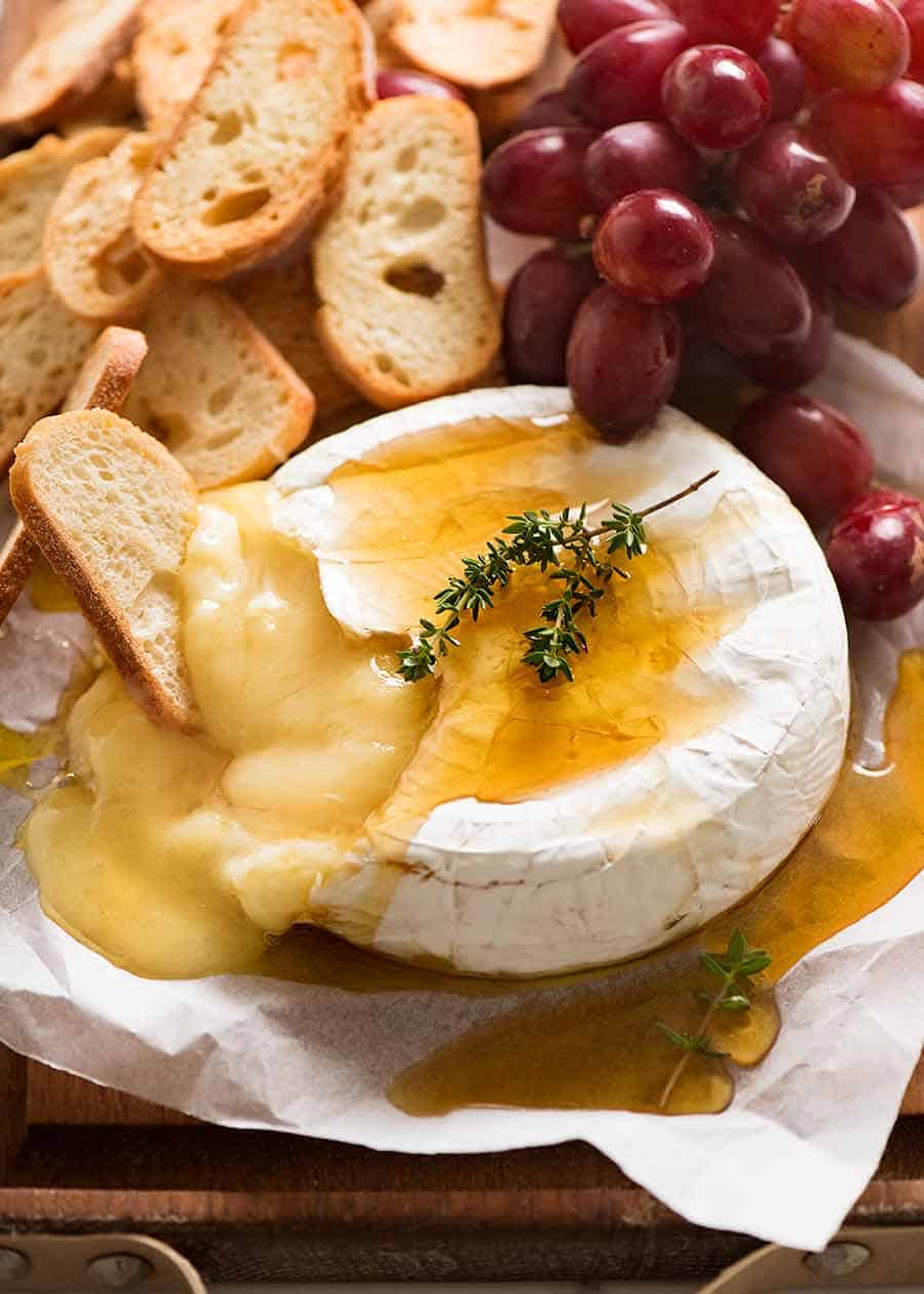 Baked Brie served with crisp breads and grapes