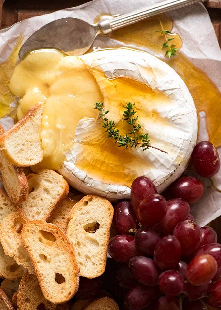 Overhead photo of Baked Brie drizzled with honey served with crispy toasted bread and grapes