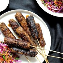 Pile of lamb koftas on a white plate with a bright red cabbage and carrot slaw on the side.