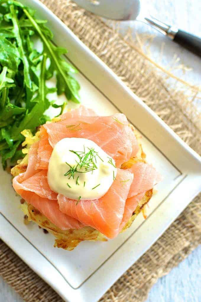 Overhead photo of Smoked Salmon Potato Rosti Stack with a rocket salad on the side.