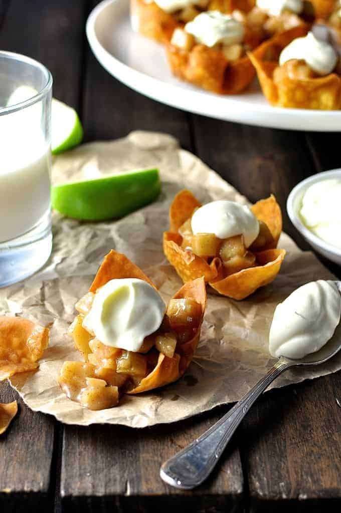 Mini Apple Pies made with wonton cups with a dollop of cream, ready for serving.