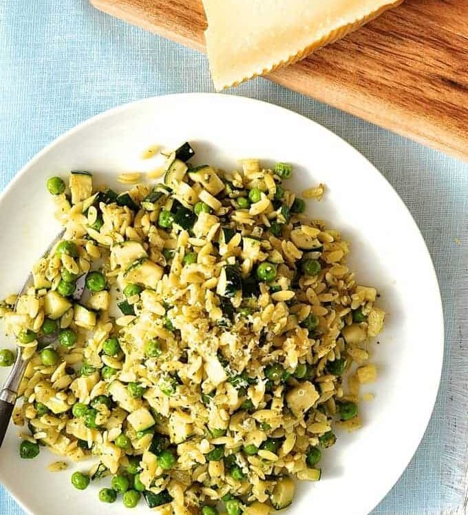 Pea, Zucchini and Pesto Orzo / Risoni on a white plate with parmesan on the side.