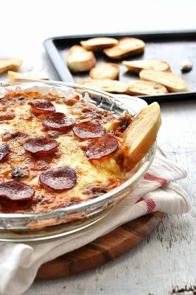 Toasted bread stuck on the side of an ultra cheesy, gooey Pizza Dip in a glass dish.