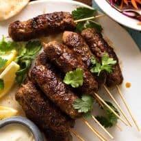 Lamb Koftas on a platter, ready to stuff into pita bread with minted salad and yogurt sauce