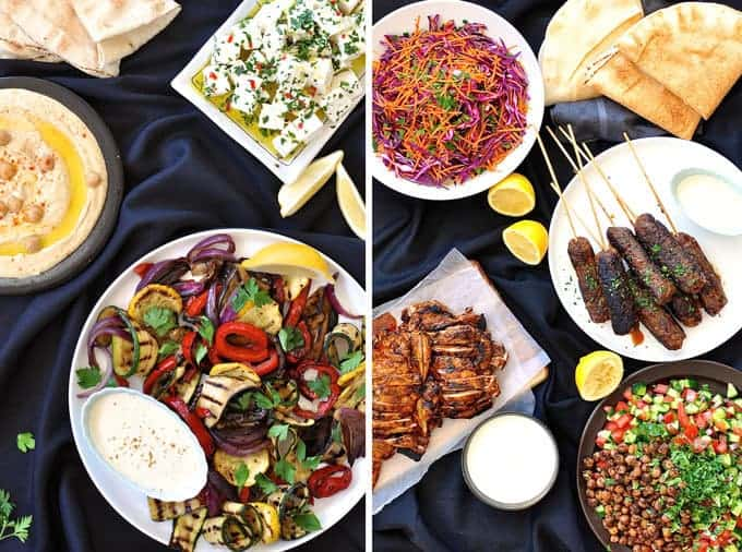 Table filled with dishes for an Arabian Feast / Middle Eastern Menu, with dishes including Chicken Shawarma, lamb kaftas, hummus, chickpea salad.