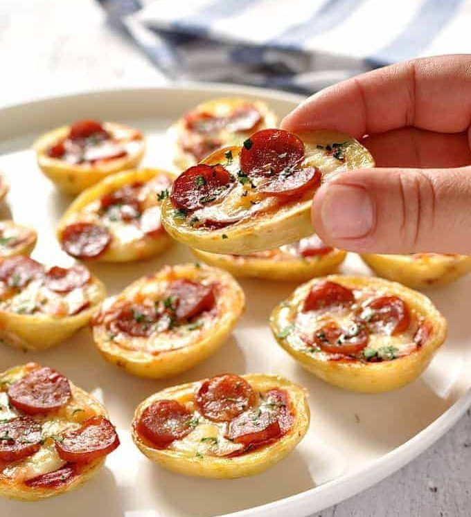 Close up of a hand holding a Mini Pizza Potato Skin with a platter of Mini Pizza Potato Skins in the background.