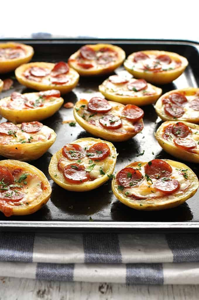 Mini Pizza Potato Skins on a black tray, fresh out of the oven.