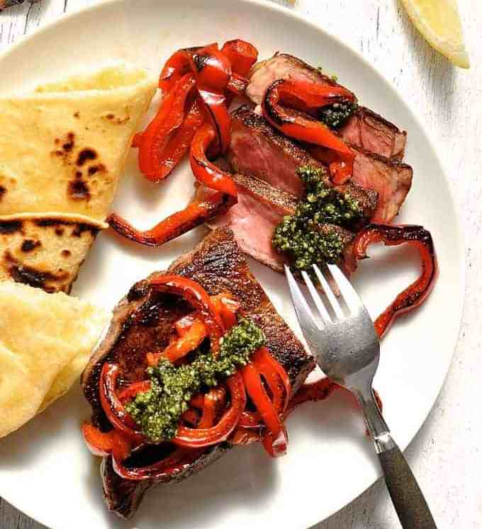 Steak with Pesto and chargrilled capsicum on a white plate, ready to be eaten.