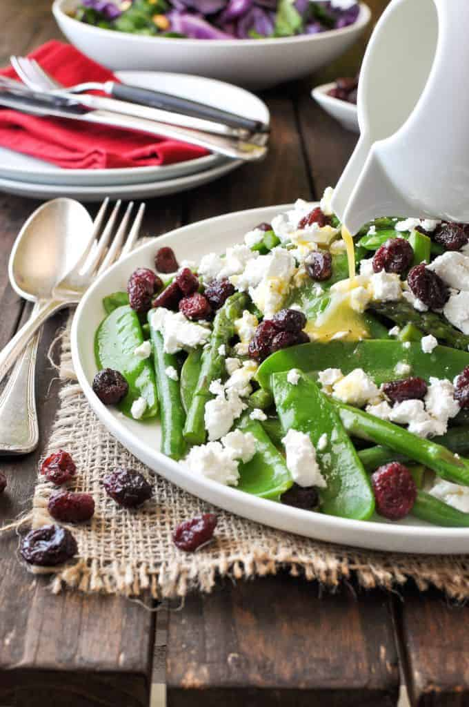 Dressing being poured over a Christmas Salad made with snow peas, asparagus, feta and cranberries.
