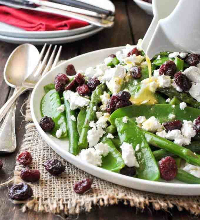 Dressing being poured over a Christmas Salad made with snow peas, asparagus, beans, feta and cranberries. Colours of Christmas!